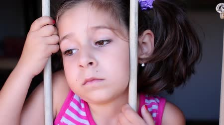 terkedilmiş : Cute little girl behind bars. Desperate little girl