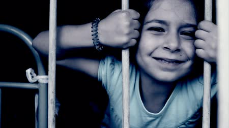 smutek : Cute little girl behind bars. Desperate little girl