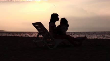 den matek : Mother and daughter hugging and kissing on a lounge by the sea. Sunrise in the background. Dostupné videozáznamy
