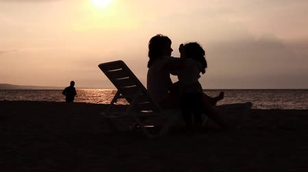 anne : Mother and daughter hugging and kissing on a lounge by the sea. Sunrise in the background. Stok Video