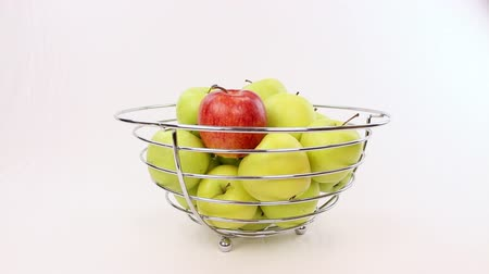 diferença : Hand chooses a red apple from a bowl with green apples, be different