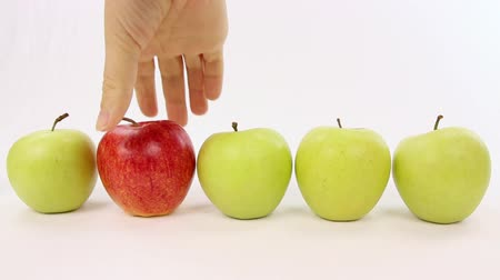 различный : Hand chooses a red apple from a line with green apples, be different Стоковые видеозаписи
