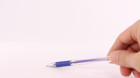 peeved : Male hand playing nervously with a pen on a white background Stock Footage