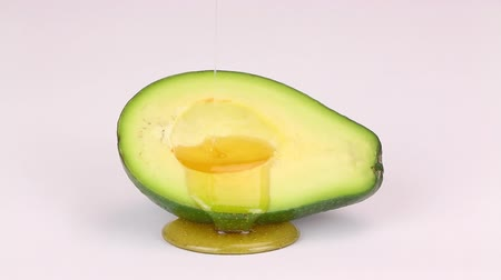 avokado : Oil drops over a half cut avocado on a white background