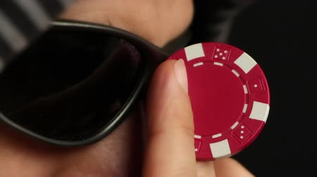 покер : Poker player adjusting his sunglasses with a red chip, close up