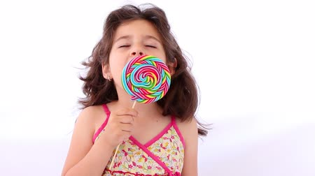леденец : Little girl licking a lollipop, close up