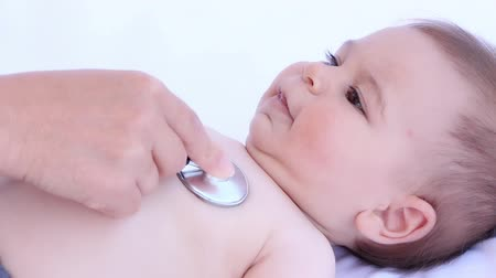 医疗保健 : Kid doctor examining happy baby boy with stethoscope on a white background 影像素材