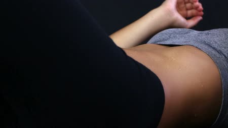 sudore : Primo piano di donna facendo sit-up su sfondo nero Filmati Stock