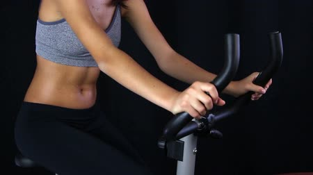 suor : Close up of a young woman riding stationary bike