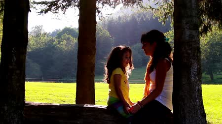 beijos : Mother and daughter hugging and kissing on tree log. Sunset in the background Vídeos