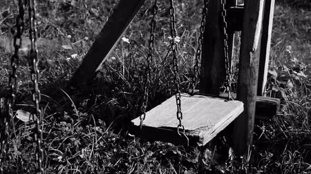 zoufalý : Black and white video of empty broken swing, concept of abandoned child