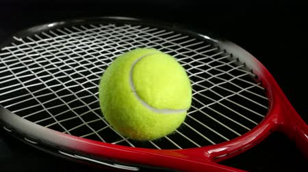 ракетка : Tennis ball bouncing over a tennis racket on a black background Стоковые видеозаписи
