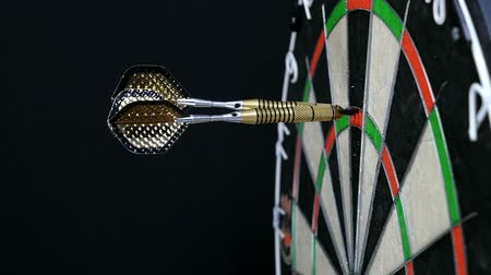dart : Slow motion of three darts hitting triple twenty on a dart board and players hand picking them up