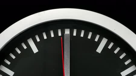 asal : Close up of a black wall clock isolated on black background, the hour hand pointing twelve