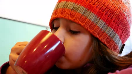 какао : Cute girl with winter hat sipping hot cocoa drink