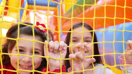 inflável : Two girls holding on the net of inflatable rubber castle playground. Recreation outdoors for kids Vídeos