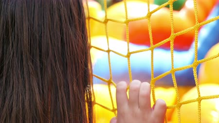 отдыха : A girl is watching children playing on inflatable rubber castle playground. Recreation outdoors for kids