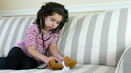 estetoscópio : Little girl with sore throat examining her ill bear toy with a stethoscope Vídeos