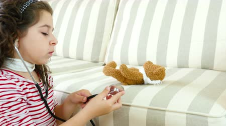 hrdlo : Little girl with sore throat examining her ill bear toy with a stethoscope Dostupné videozáznamy