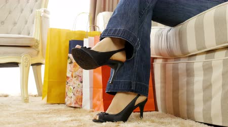 one woman only : Woman returns at home with shopping bags tired but satisfied legs only