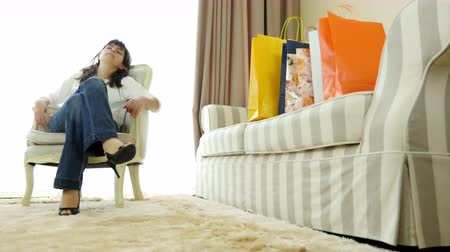 sitting room : Woman returns at home with shopping bags tired but satisfied Stock Footage