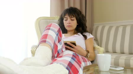 longo : Woman in pajamas is reading a book at home a cup of coffee and a mobile phone on the table
