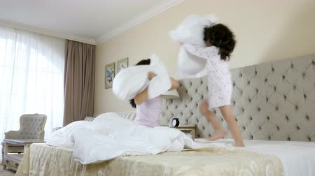 almofada : Mother and daughter having pillow fight in the bedroom