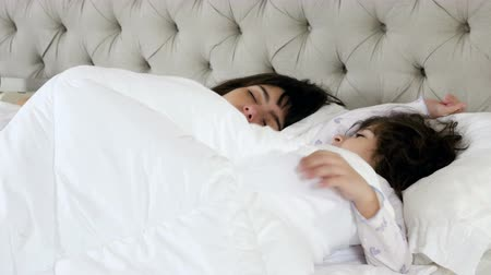 мама : Mother kissing her little daughter while she is sleeping in bed Стоковые видеозаписи