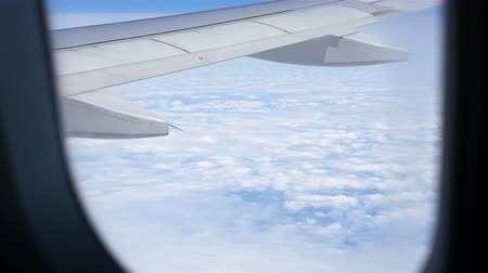 szárny : Airplane window view to the blue sky and clouds. Transportation Stock mozgókép