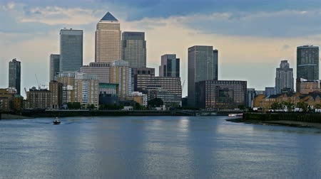 docklands : Boats floating on river Thames at sunset, London, business center Canary Wharf on the background