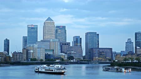 docklands : Timelapse of boats floating on river Thames at sunset, London, business center Canary Wharf on the background