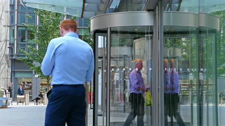 podnikatel : UNITED KINGDOM, LONDON - JUNE 14, 2015: Businessmen walk in and out a modern office building in London city, England