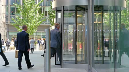 aktywność : UNITED KINGDOM, LONDON - JUNE 14, 2015: Businessmen walk in and out a modern office building in London city, England