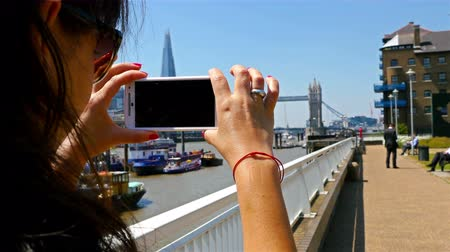 fényképész : Tourist woman taking photo of Tower Bridge and the Shard in London city, United kingdom
