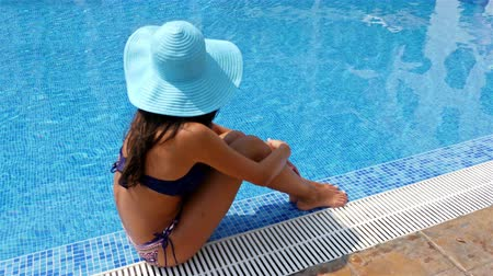 opalenizna : Young woman in swimming suit and blue hat sitting on the edge of a swimming pool and taking sunbath