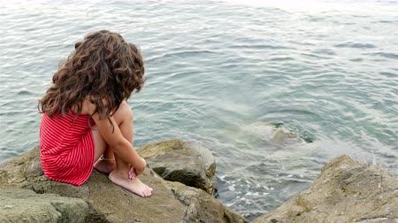 сидеть : Little girl in red summer dress sitting on the rocks on the sea shore