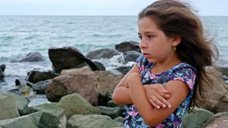 ветер : Sorrowful little girl standing alone on the rocks by the stormy sea