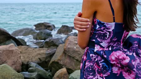 ventoso : Young woman standing on the rocky shore by the sea at sunset, her dress fluttering in the wind Stock Footage
