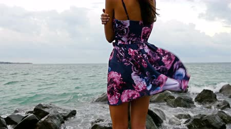 Young woman standing on the rocky shore by the sea at sunset, her dress fluttering in the wind Stock Footage