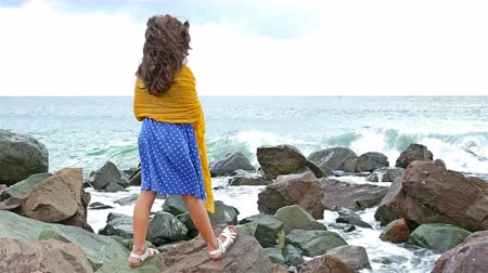 Little girl in a dress and scarf standing on the rocks and looking to the stormy sea