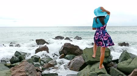Young woman with summer dress, scarf and hat standing on the rocky shore by the sea at sunset, sea waves crash on the rocks