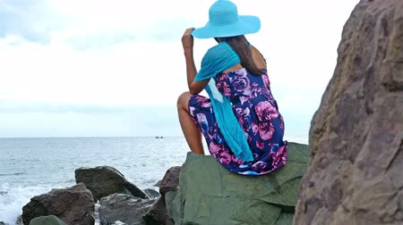Young woman with summer dress and a hat sitting on the rocky shore by the sea, cloudy sky above, sea waves crash on the rocks