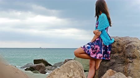 Young woman with summer dress sitting on the rocky shore by the sea, cloudy sky above, sea waves crash on the rocks Stock Footage