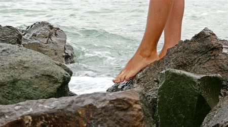Bare female legs passing on rocky sea shore