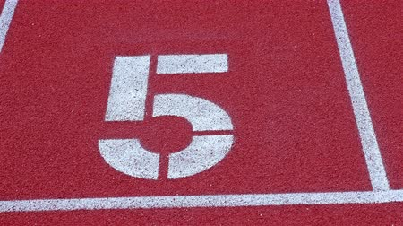 five striped : Slow dolly to a number 5 on a running track, counter number five