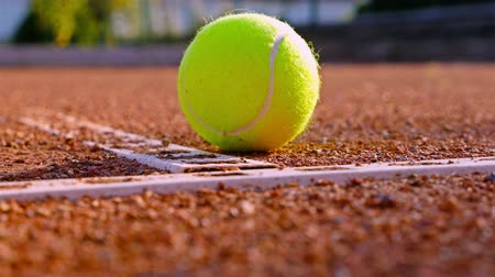 tennis game : A rolling tennis ball stops at a line on a red tennis court Stock Footage