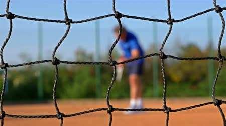 tennis game : Tennis Player serving Tennis Ball With Tennis Racket On Clay Court, net in front, dolly Stock Footage