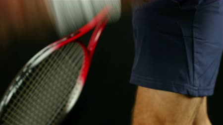 Tennis player prepares for serving, black background Stock Footage