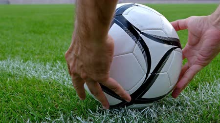 match : Footballsoccer concept. Football player hands putting a soccer ball on the corner point of the football field