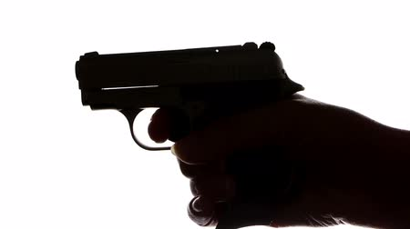 Silhouette of hands loading a gun and shooting Stock Footage